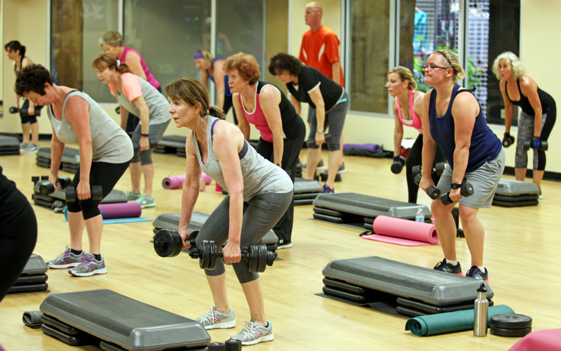 People lifting weights in a group exercise class