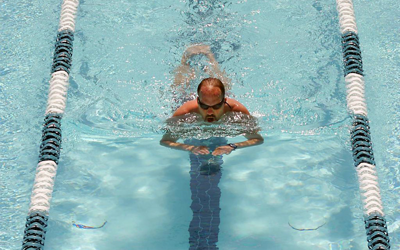 Man swimming in an outdoor pool