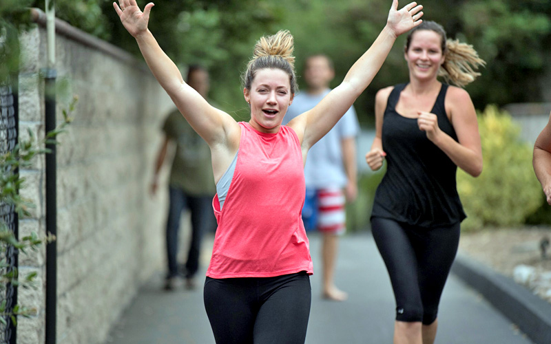 Woman smiling while running outside